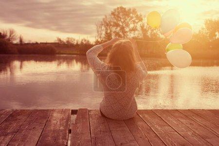 Photo pour Femme assise sur le banc dans le parc - image libre de droit