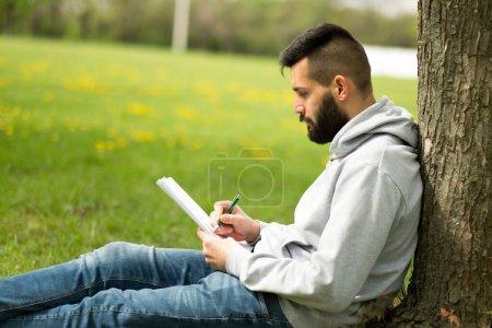 Photo pour Beau barbu homme apprenant dans le concept de parc - image libre de droit
