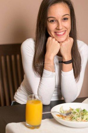 Photo pour Jeune femme manger de la salade dans la cuisine - image libre de droit