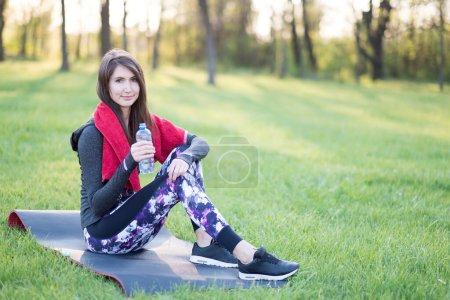 Photo pour Femme fitness avec bouteille d'eau dans le parc de printemps - image libre de droit