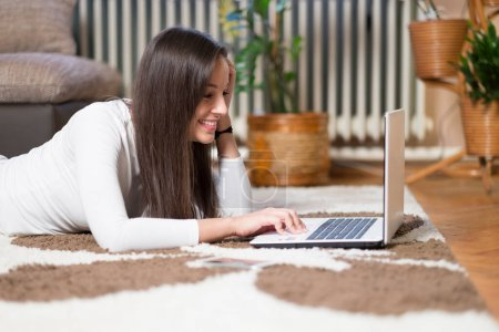 Photo for Young woman using laptop at home - Royalty Free Image