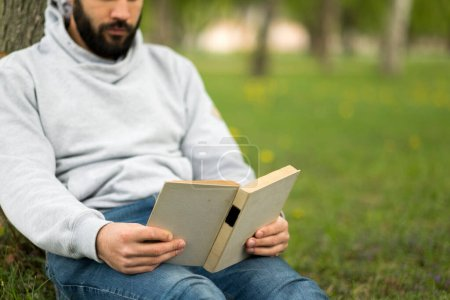 Photo for Young man reading book in park - Royalty Free Image