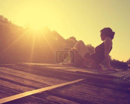 Photo pour Photo vintage de jeune femme se relaxant avec son chien au bord du lac au coucher du soleil - image libre de droit
