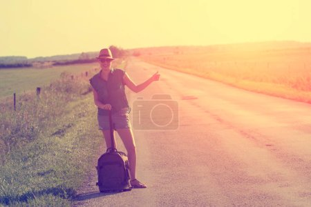 Photo for Young man with suitcase standing on the road - Royalty Free Image