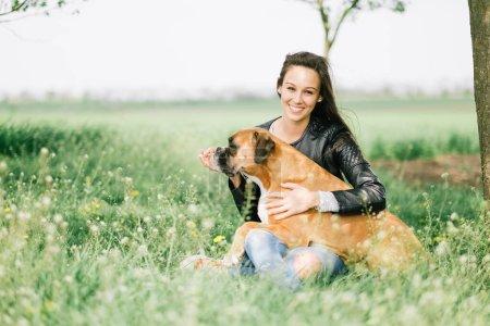 Photo pour Jeune femme avec un chien dans le parc. - image libre de droit