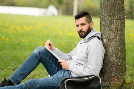 Photo pour Jeune homme assis sur le banc et le livre de lecture - image libre de droit