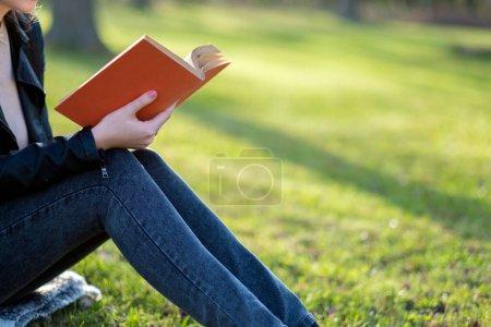 Photo pour Jeune femme lecture livre dans le parc - image libre de droit