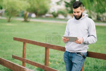 Photo pour Jeune homme avec tablette dans le parc - image libre de droit