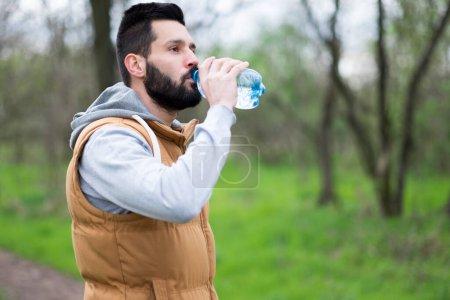 Photo pour Jeune homme buvant de l'eau de bouteille de bière - image libre de droit
