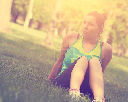 Photo pour Jeune femme s'étirant avant de courir dans le parc - image libre de droit