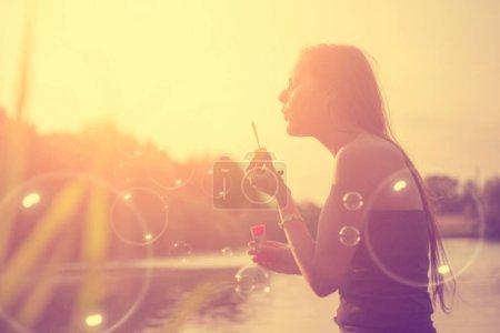 Photo pour Jeune femme avec écouteurs écoutant de la musique dans le parc - image libre de droit