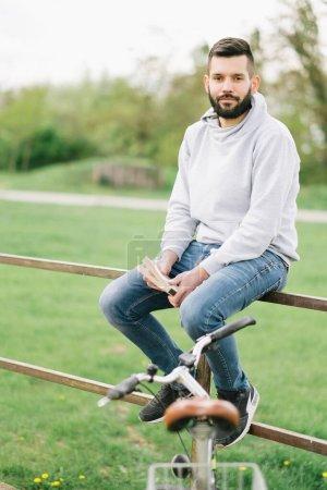 Photo pour Jeune homme beau assis sur le banc et tenant un vélo - image libre de droit