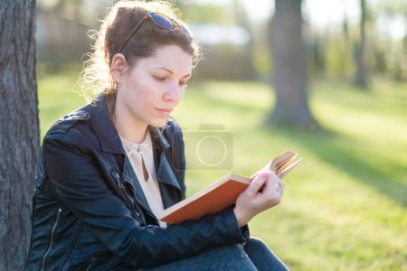 Photo for Young woman reading a book in the park - Royalty Free Image