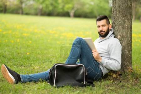 Photo for Young man sitting on the grass and listening to music - Royalty Free Image
