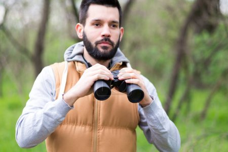 Photo pour Jeune homme avec jumelles dans le parc - image libre de droit