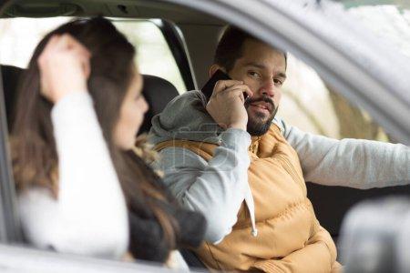 Photo pour Jeune homme parlant sur téléphone portable tout en conduisant la voiture - image libre de droit