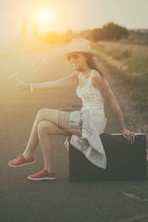 Photo pour Jeune femme avec valise sur la route - image libre de droit