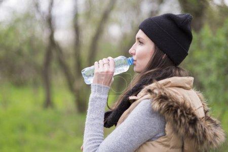 Photo pour Jeune femme buvant l'eau d'une bouteille de temps froid - image libre de droit