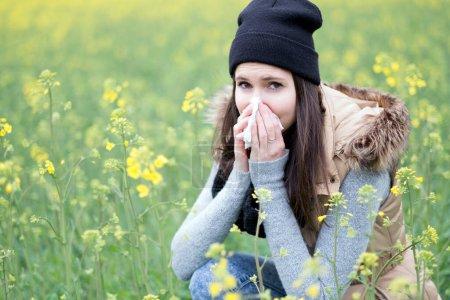 Photo pour Jeune femme soufflant des fleurs de pissenlit dans le parc - image libre de droit
