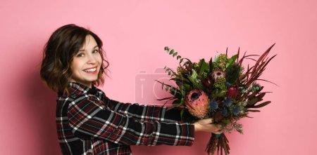 Photo pour Côté voir le profil de jeune femme séduisante dans un sombre dresst damier tenant le bouquet de fleurs et de vous donner. D'intérieur, studio, coup, isolé sur un fond rose, copier l'espace - image libre de droit