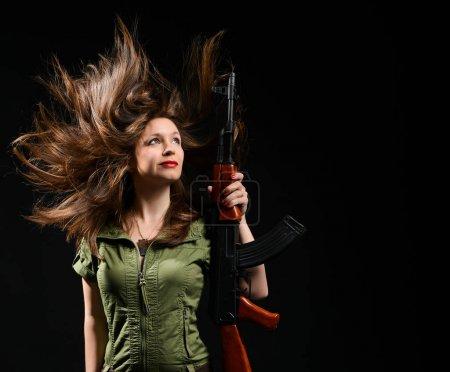 Photo pour Jeune fille brune dans une robe kaki verte tenant un pistolet sur un fond de studio noir . - image libre de droit