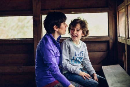Mother with her seven year old daughter laughing in a cabin in the countryside. Lifestyle concept.