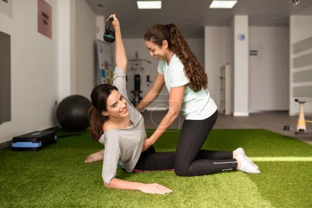 Physical therapist assisting young caucasian woman with exercise with dumbbell during rehabilitation in the gym at hospital. Female physiotherapist training a patient in physiotherapy center.