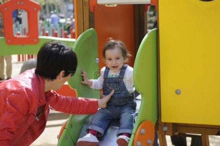 Photo pour Bonne petite fille jouant dans une Cour de récréation urbaine. - image libre de droit