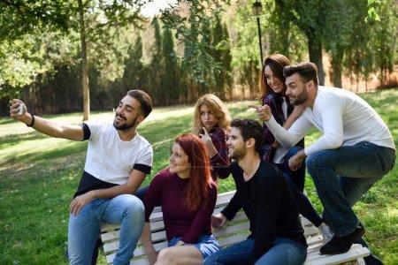 Photo pour Groupe d'amis prenant selfie dans le parc urbain. Cinq jeunes portant des vêtements décontractés . - image libre de droit
