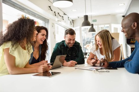 Photo for Five young people studying with laptop and tablet computers on white desk. Beautiful girls and guys working toghether wearing casual clothes. Multi-ethnic group smiling. - Royalty Free Image