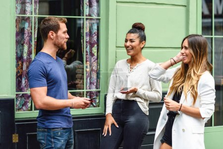 Three multiethnic people laughing outdoors with smart phone in their hands. Multiracial group of friends having fun in urban background.