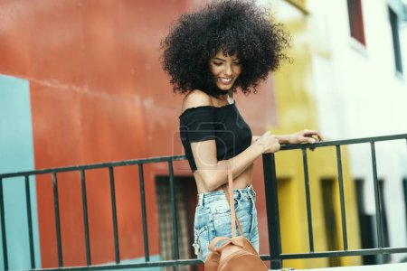 Photo for Young mixed woman with afro hair near a modern colorful building. Female wearing casual clothes in urban background. Lifestyle concept - Royalty Free Image