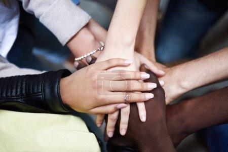 Photo pour Vue rapprochée de dessus des jeunes gens mettant leurs mains ensemble. Amis avec pile de mains montrant l'unité et le travail d'équipe. - image libre de droit