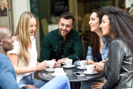 Photo pour Groupe multiracial de cinq amis prenant un café ensemble. Trois femmes et deux hommes au café, parlant, riant et appréciant leur temps. Concepts de style de vie et d'amitié avec des modèles réels - image libre de droit