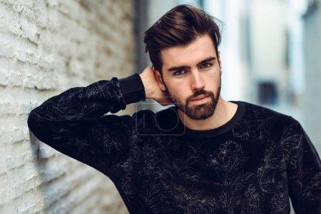 Photo pour Jeune barbu homme, modèle de mode, à la recherche à la caméra à fond urbain, porter des vêtements décontractés. Mec avec une barbe et une coiffure moderne dans la rue. - image libre de droit