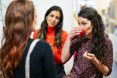 Photo pour Groupe multiethnique de trois amies heureuses buvant du café dans un café-bar . - image libre de droit