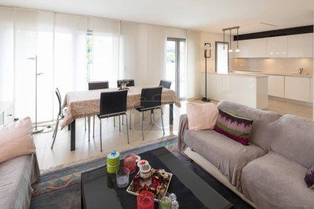 Foto de Sala de estar con sofás, mesa con sillas para comer y una cocina moderna. Interior del apartamento de espacio abierto - Imagen libre de derechos