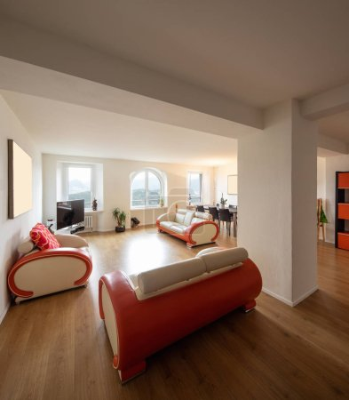 Living room with leather and parquet design sofa. Large windows enter a lot of natural light. Nobody inside