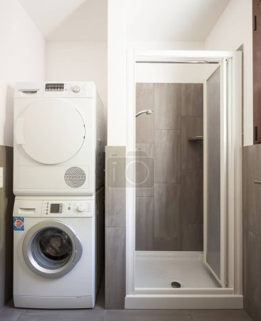 Front view of shower, washing machine and dryer. Concept, nobody inside