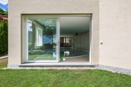 Détail de fenêtre avec piscine, de l'extérieure de la villa. Personne à l'intérieur