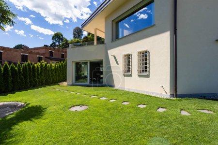 Photo pour Villa avec grand jardin pendant une journée d'été. Personne à l'intérieur - image libre de droit