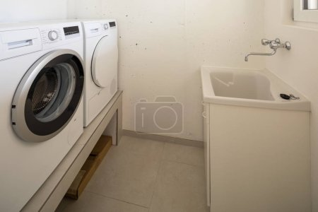 Laundry with washing machine, dryer and sink. Nobody inside