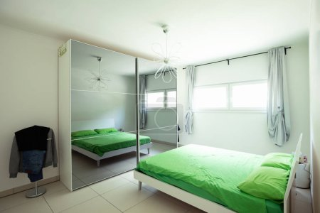 Room with double bed and green blanket with bright window, Nobody inside