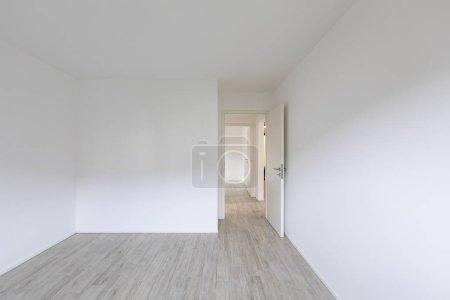 Photo pour Salle vide aux murs blancs et ouvrir la porte à droite. Personne à l'intérieur - image libre de droit
