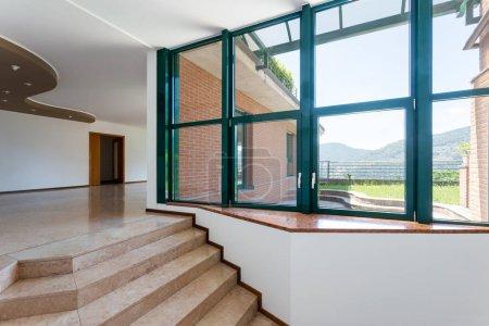 Photo pour Entrée de l'appartement de luxe avec marbre et grandes fenêtres sur le jardin privé. Personne à l'intérieur - image libre de droit