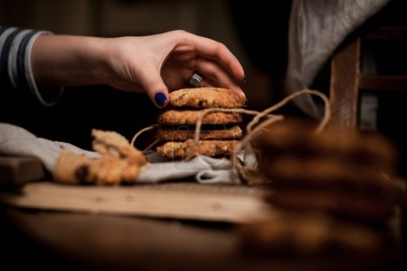 Photo for Photo shows a hand holding a crunchy homemade almond biscotti in front of hundreds of biscotti - Royalty Free Image