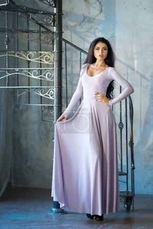 Photo for Stylish brunette woman in elegant long pastel purple dress in luxury interior - Royalty Free Image