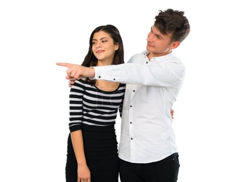 Photo pour Jeune couple pointant du doigt sur le côté et présentant un produit sur fond blanc isolé - image libre de droit