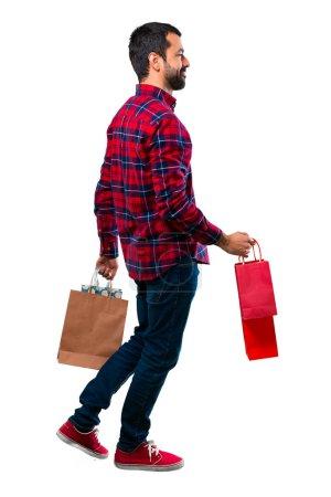 Bel homme tenant beaucoup de sacs à provisions
