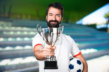 Lucky football player holding a soccer ball holding a trophy on a football pitch